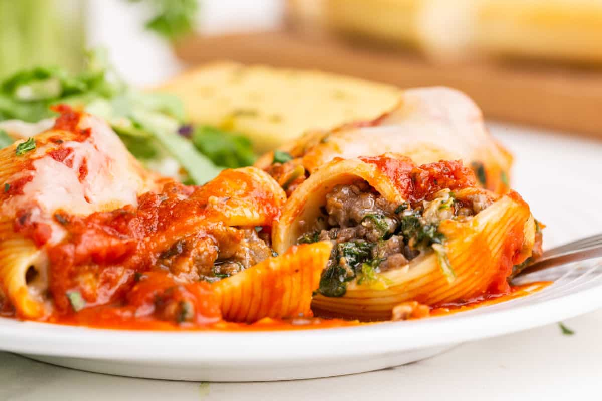 Stuffed shells covered in cheese and pasta sauce on a serving plate.