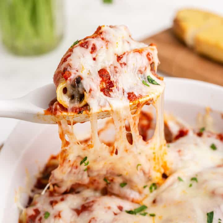 Cheesy sausage stuffed shells being spooned out of baking dish.