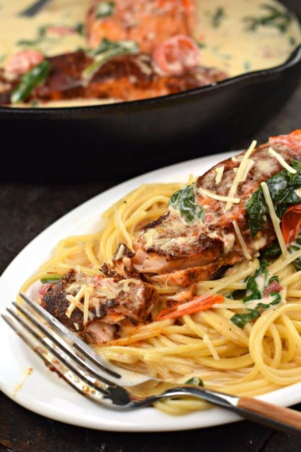 Blackened Salmon with Creamy Tuscan Garlic Sauce served over a bed of pasta. Flaky salmon with incredible flavor!