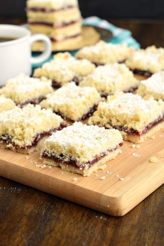 Shortbread cookie bars with a raspberry filling and powdered sugar on top, cut into squares on a wooden cutting board.