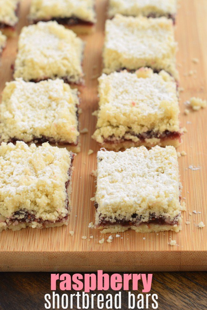 Raspberry Crumb Bars topped with powdered sugar cut into squares on a wooden cutting board.