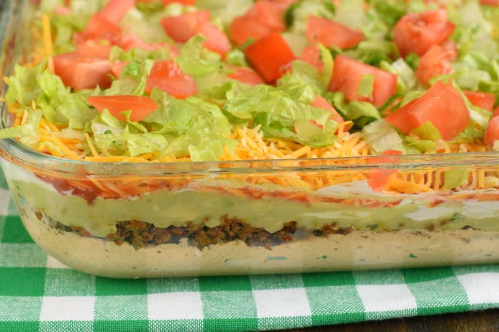 7 Layer Dip packed with layers of Cream Cheese, Sour Cream, Ground Beef (and/or Beans), Guacamole, Salsa, Cheese, and more!