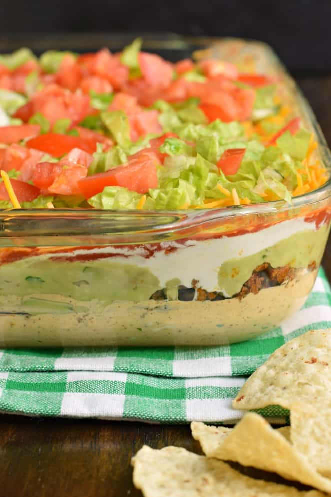 Seven layer dip in a glass bowl served with tortilla chips.