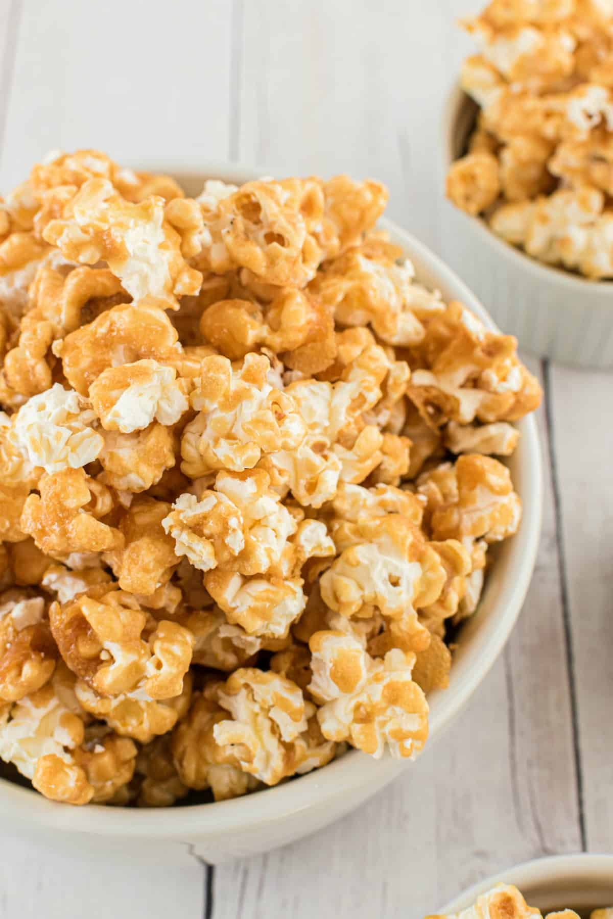 Caramel corn in a white bowl for serving.