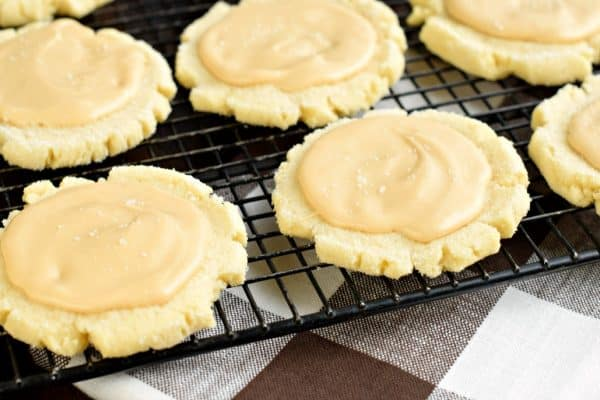 These Caramel Frosted Sugar Cookies are irresistible. Chewy sugar cookies with a no-chill dough topped with a sweet and salty caramel frosting!