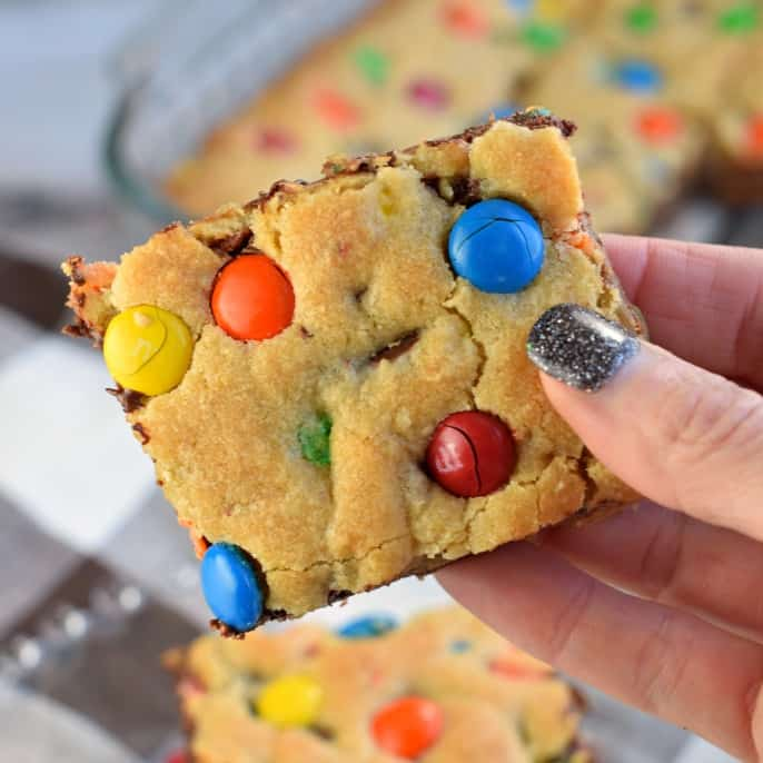 Close up of slice of chocolate chip cookie bar with colorful m&m candies.