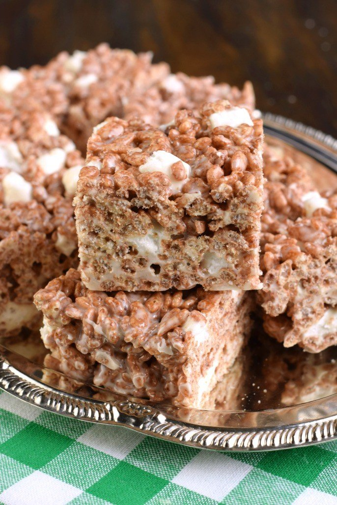 Chocolate rice krispie treats cut into squares on a silver serving tray.