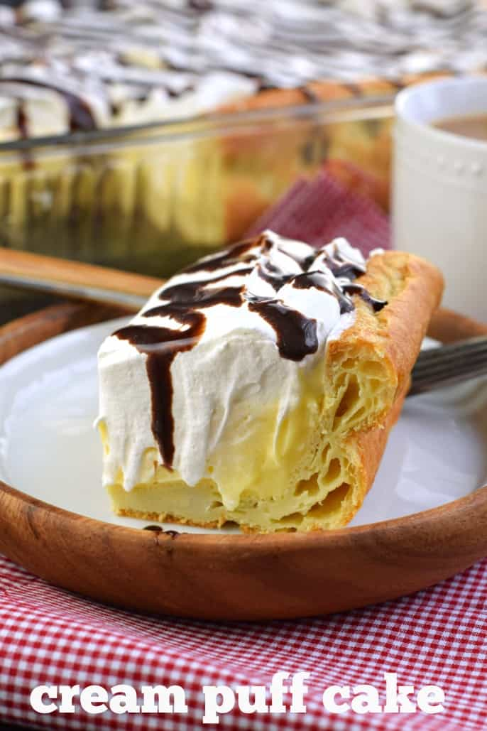 Slice of cream puff cake with flaky crust and topped with chocolate syrup, on a wooden plate and red checkered napkin.