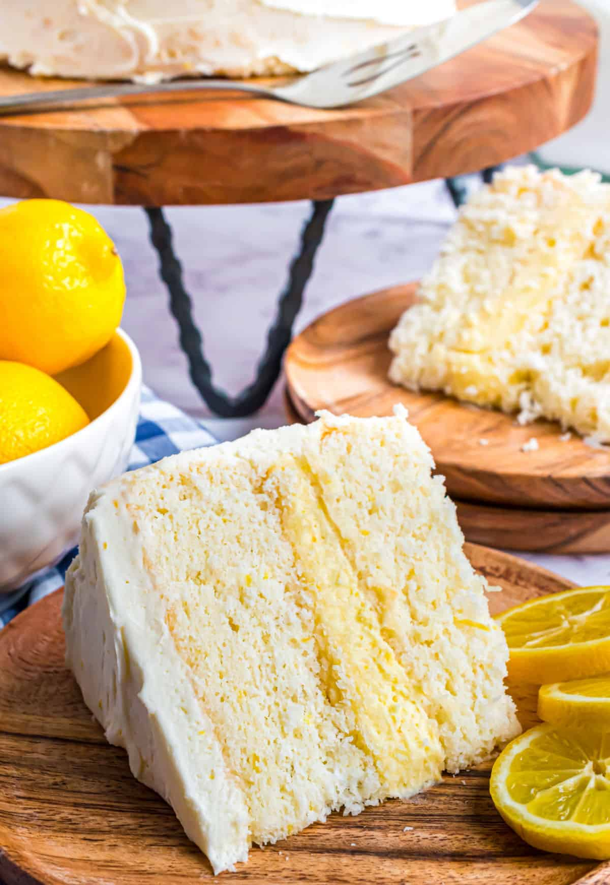 Slice of lemon layer cake with lemon curd filling on a wooden plate.