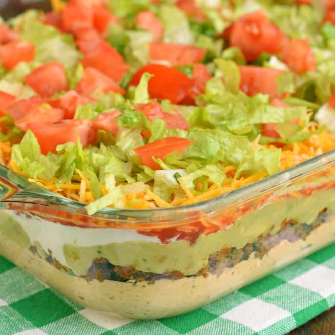 The Ultimate 7 Layer Dip recipe is packed with layers of Cream Cheese, Sour Cream, Ground Beef (and/or Beans), Guacamole, Salsa, Cheese, and more!