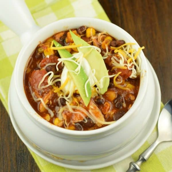 Hearty and flavorful, this fix it and forget it Slow Cooker Chicken Enchilada Chili recipe is delicious!