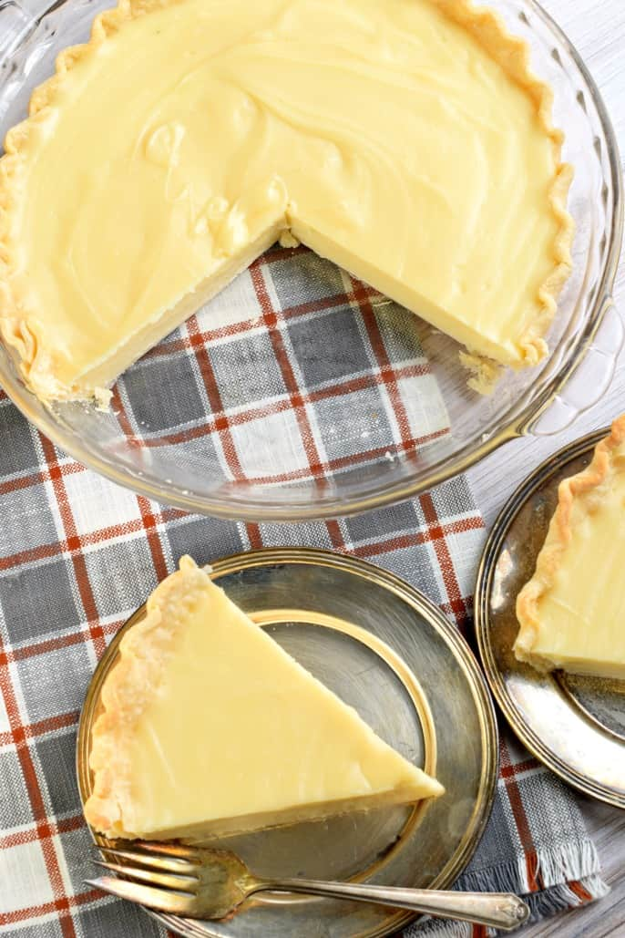 Slices of sugar cream pie removed from a clear glass pie plate and served on a silver plate with fork.