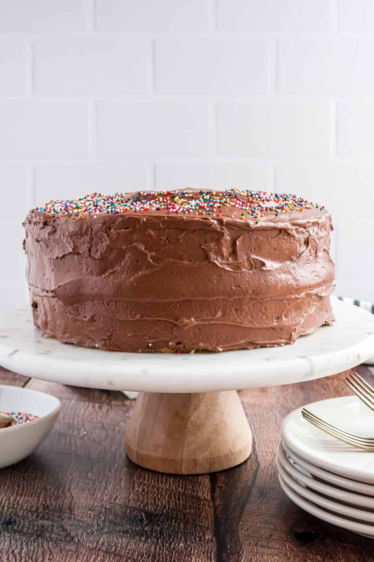 Yellow birthday cake with chocolate frosting and sprinkles on a white cake platter.
