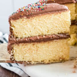 Two layers of yellow cake with chocolate frosting and sprinkles on a cake platter.