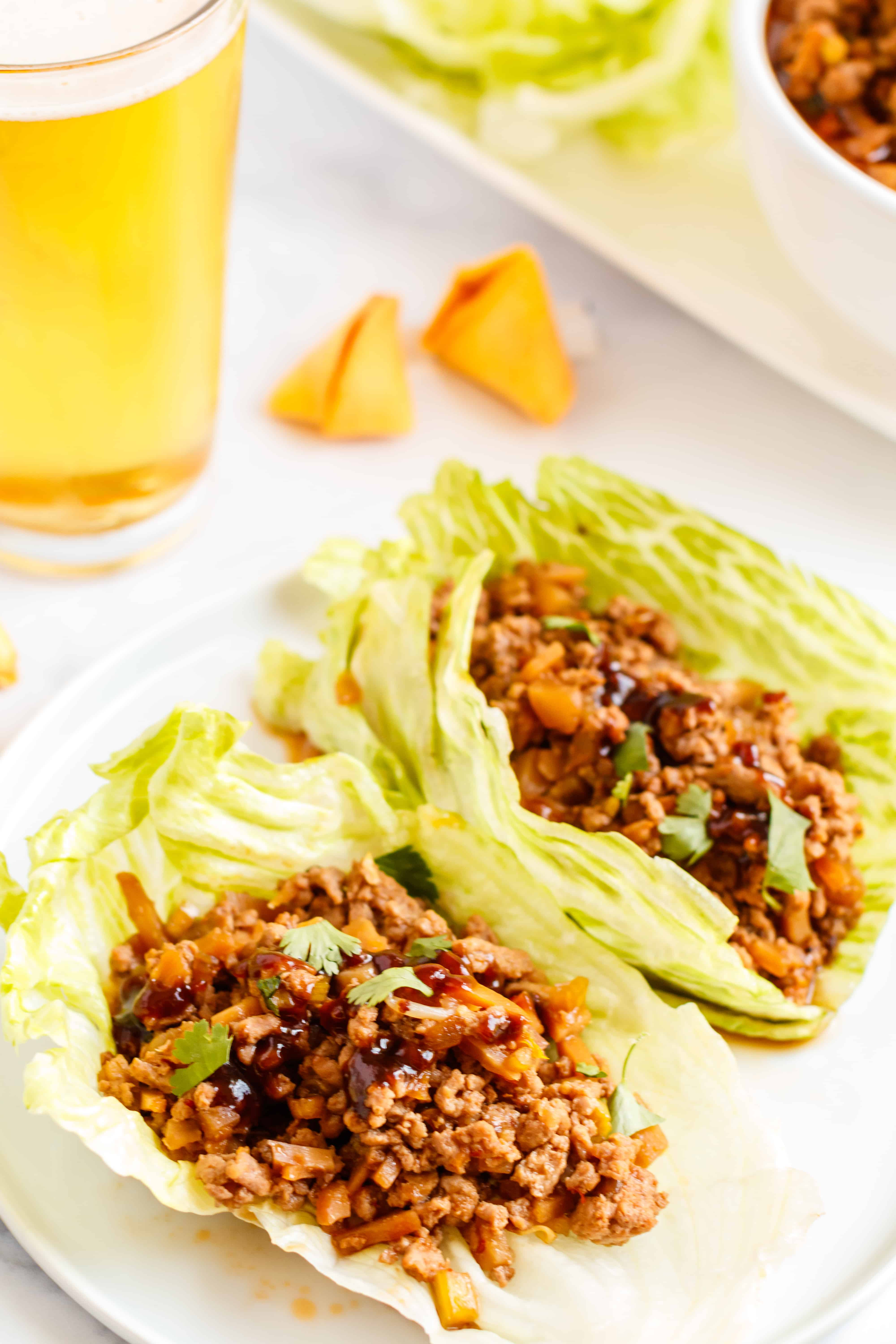 Lettuce wraps filled with crockpot meat, one a white plate.