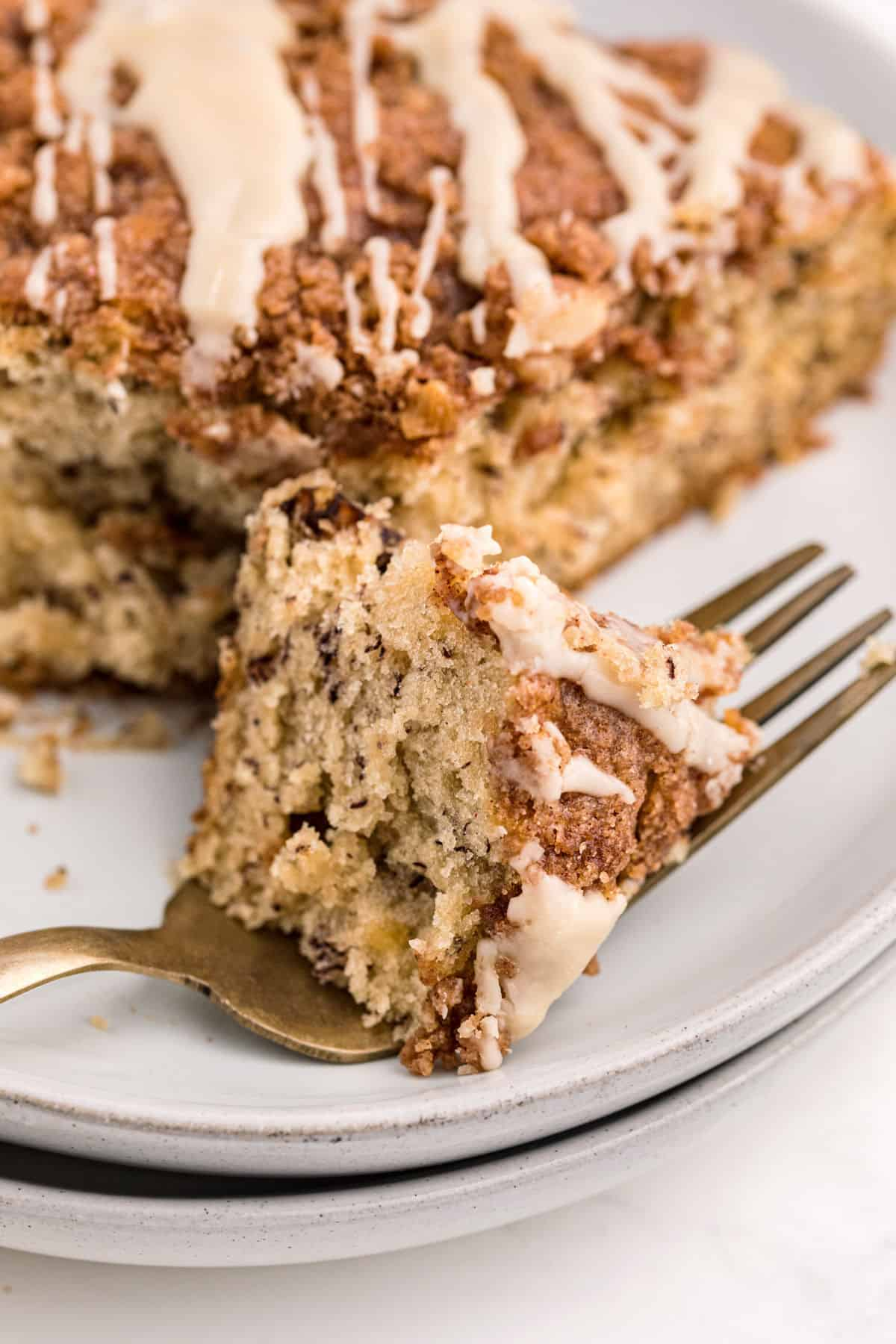 Slice of banana coffee cake with one bite on a fork.