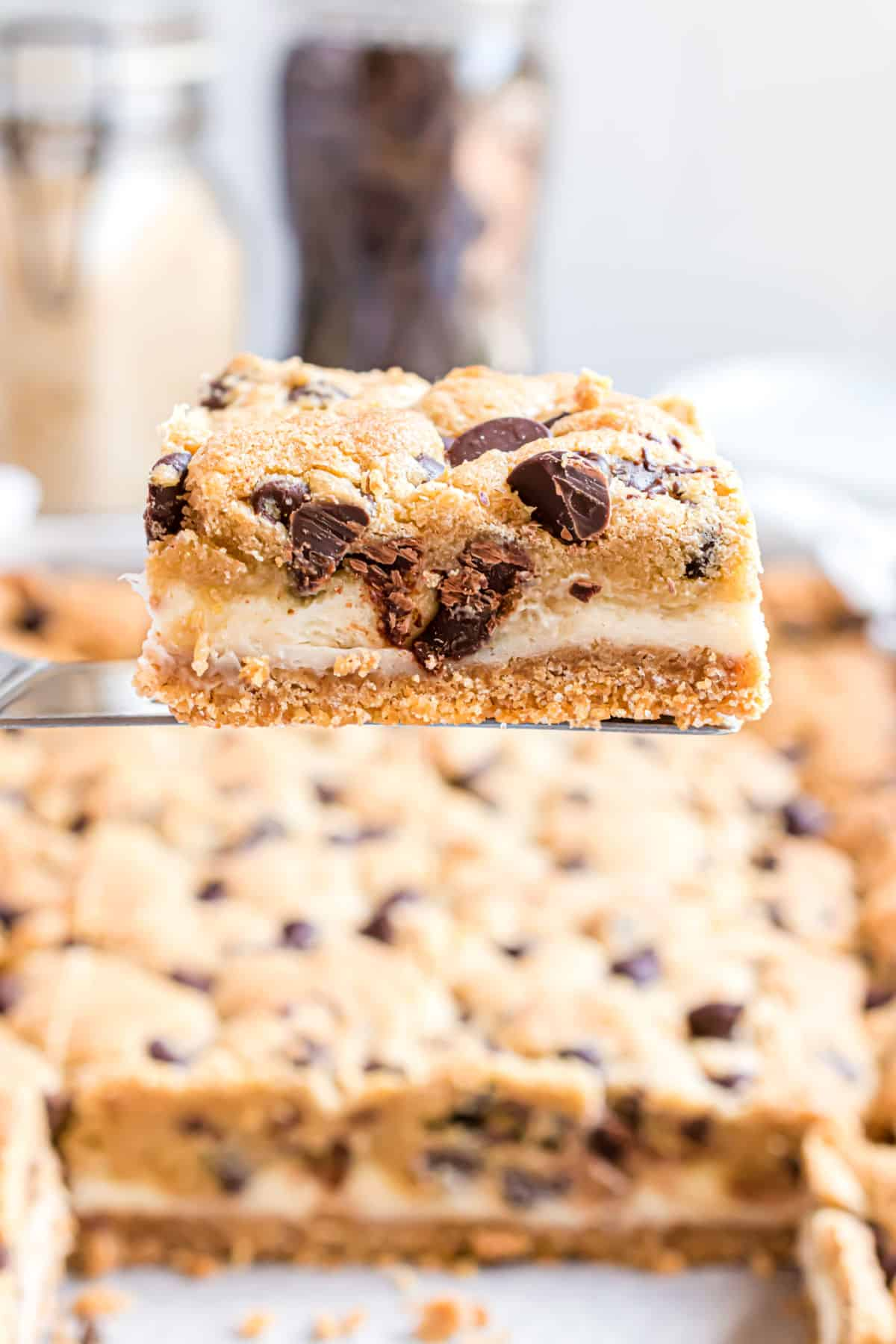 Chocolate chip cheesecake bar on a spatula being removed from pan.