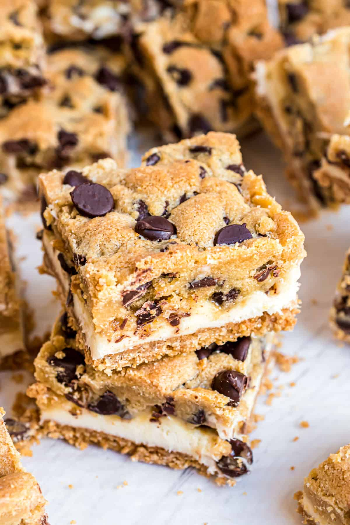 Chocolate chip cookie bars with cheesecake filling stacked on top of each other.
