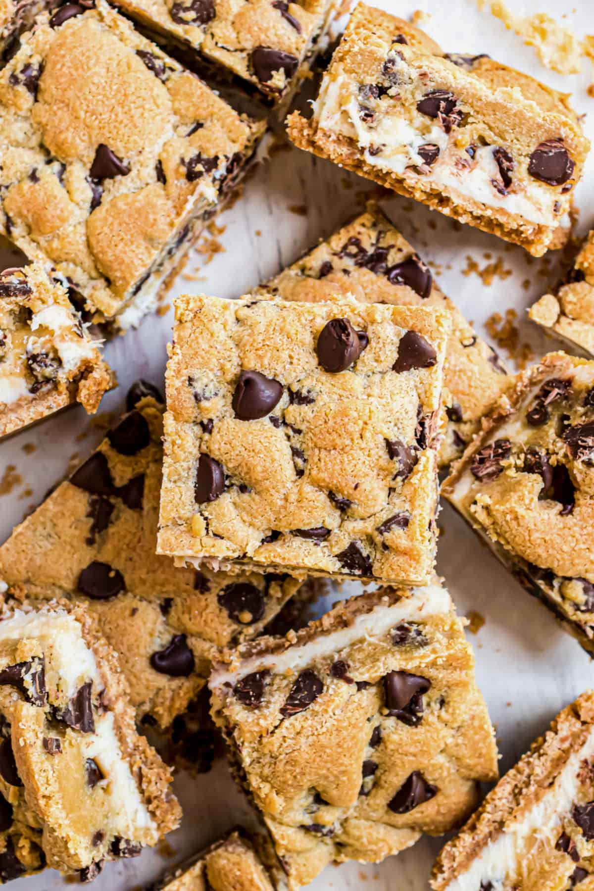 Chocolate chip cheesecake cookie bars arranged on parchment paper.