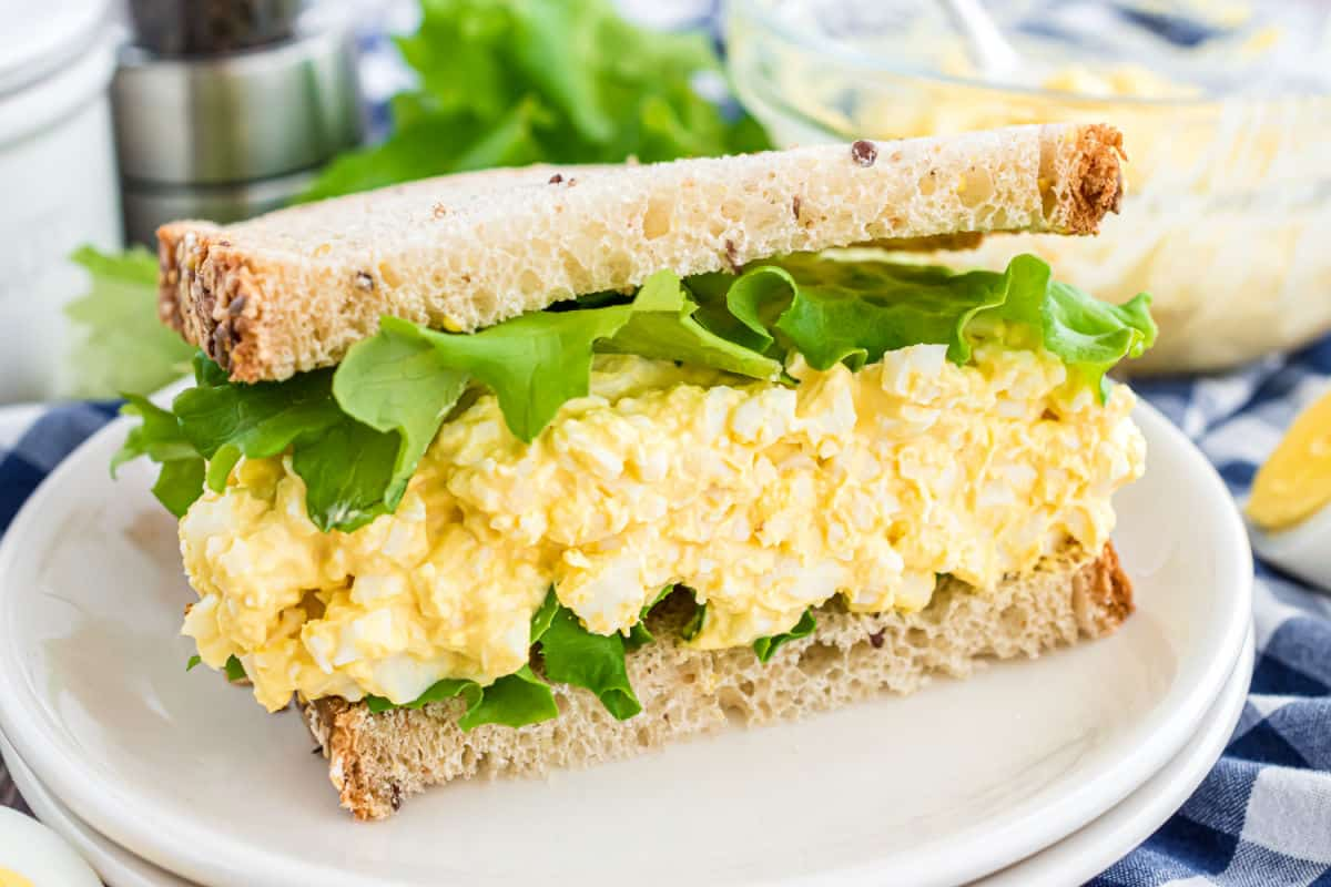 Half of an egg salad sandwich with lettuce on a white plate.