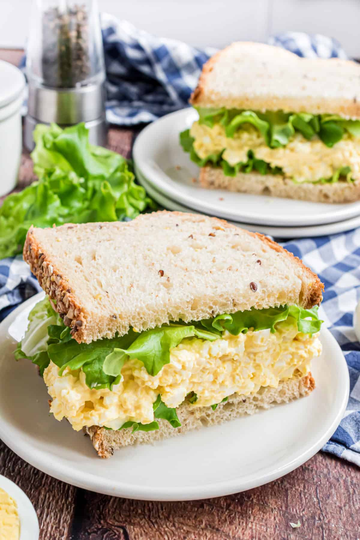 Egg salad on white bread with lettuce.