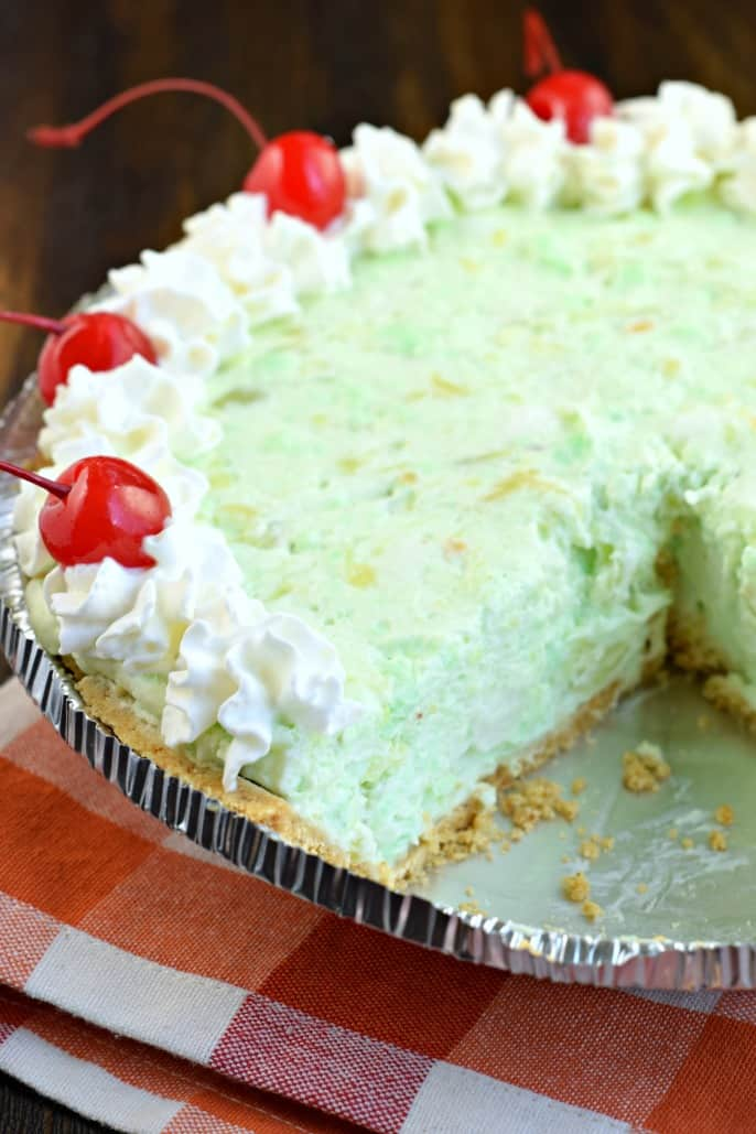 Pistachio pie in a graham cracker crust topped with whipped cream and maraschino cherries. One slice removed.
