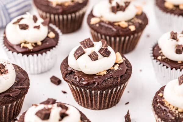 Chocolate s'mores cupcakes on marble counter.
