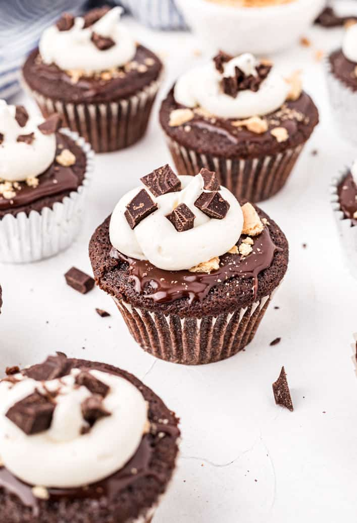 Chocolate smores cupcakes topped with ganache and frosting with chunks of graham cracker crumbs.
