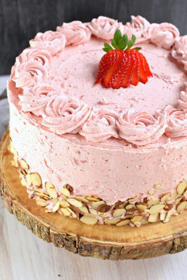 This gorgeous, from scratch, Strawberry Almond Cake recipe features a moist almond layer cake with strawberry buttercream. Fresh sliced almonds and strawberries to added flavor and texture!