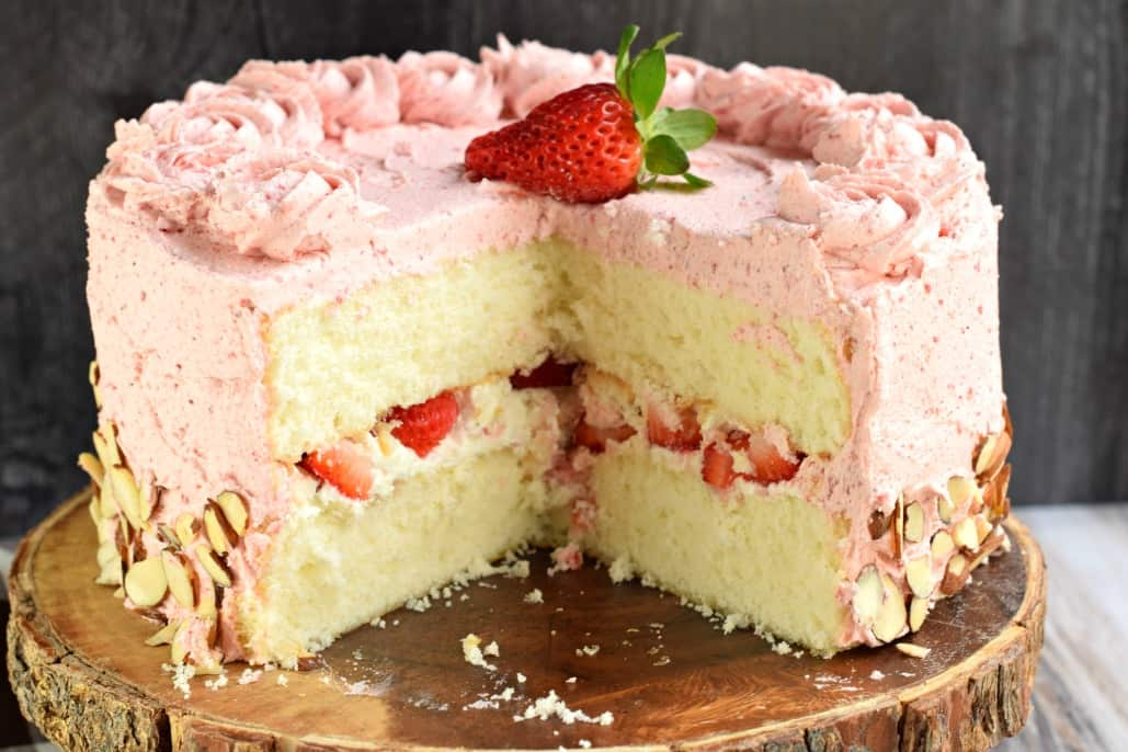 Strawberry Layer cake with big slice removed. On a wooden cake plate.