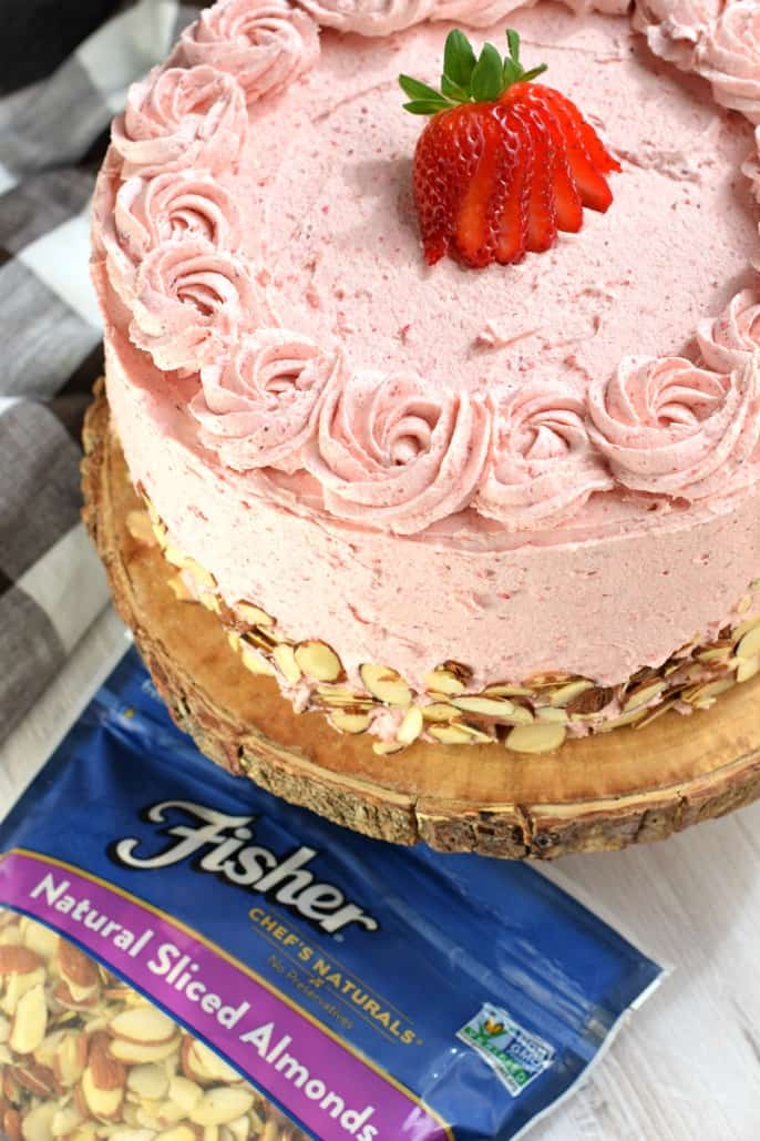 Strawberry Almond Cake on a wooden cake stand with a bag of Fisher Nuts Almonds.
