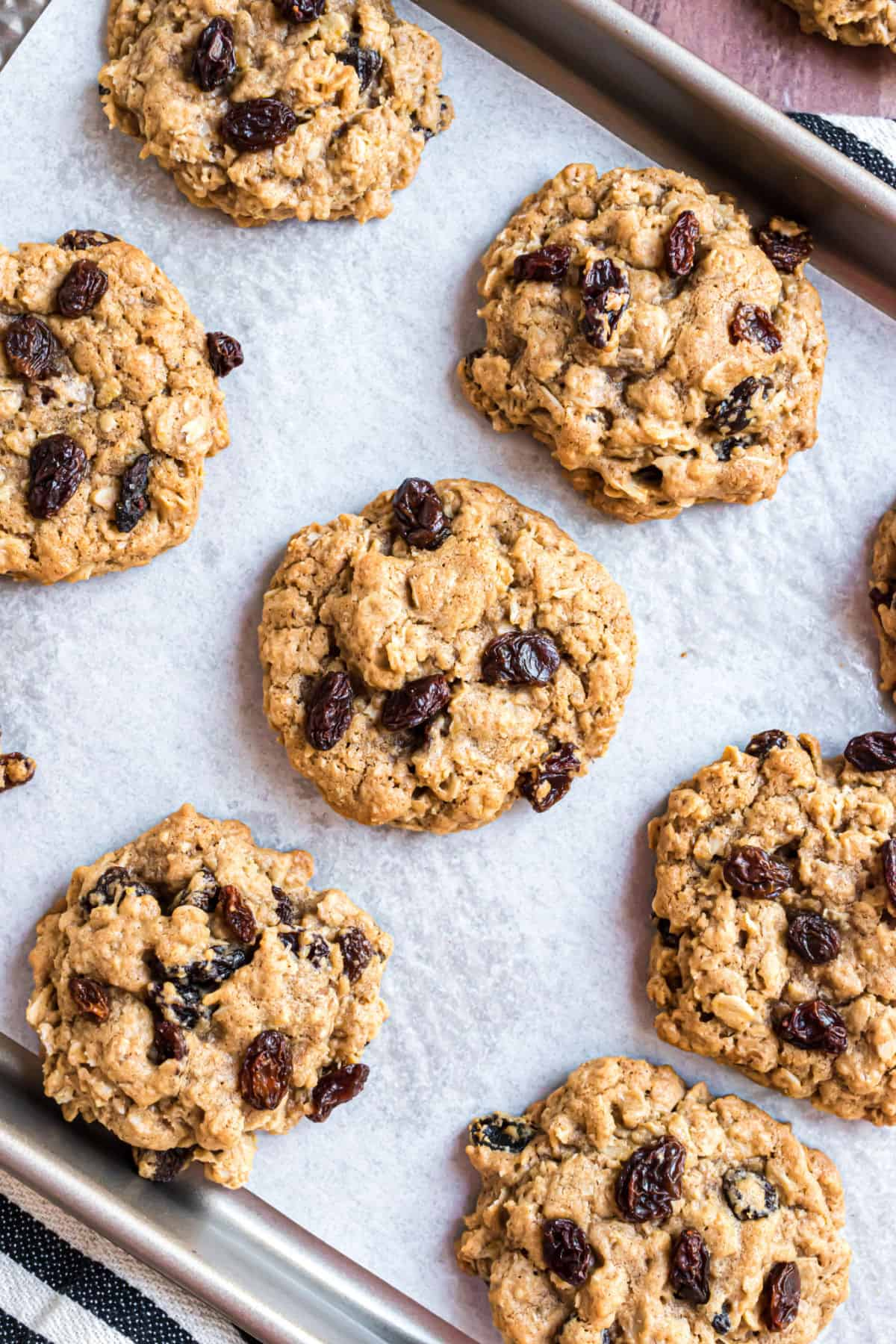 Soft and chewy oatmeal raisin cookies on a parchment paper lined cookie sheet.