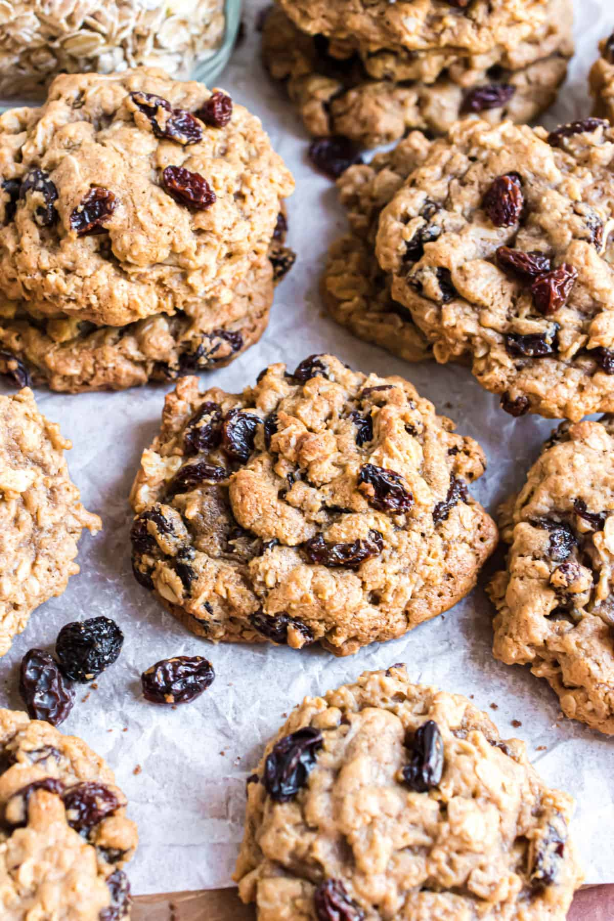 Thick oatmeal raisin cookies stacked on parchment paper lined cookie sheet.