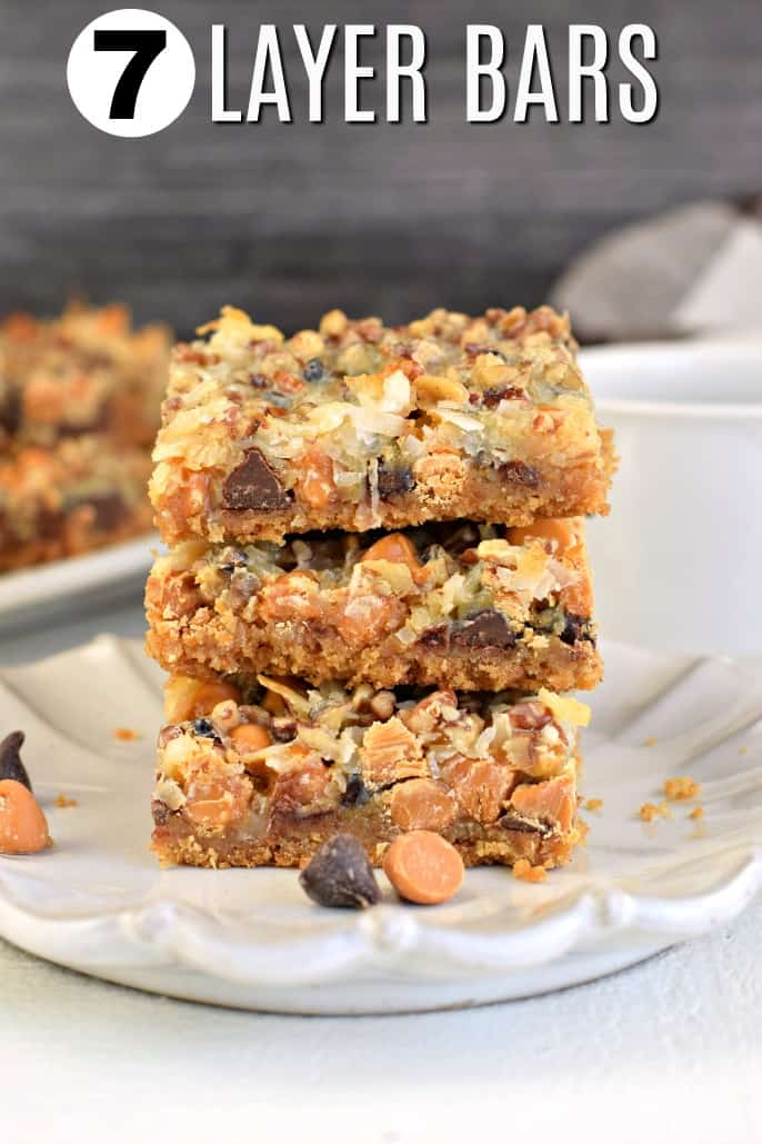 Stack of 3 seven layer bars on a white scalloped plate.
