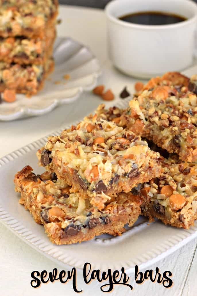 7 Layer bars on a white plate with a white mug of coffee.