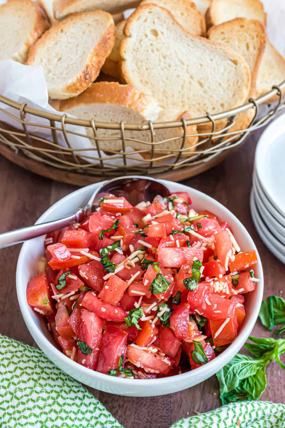 Bruschetta in a white bowl with toasted bread in wire basket.