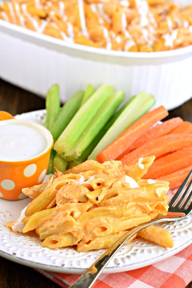 Buffalo pasta served on a white plate with carrot and celery sticks on the side.