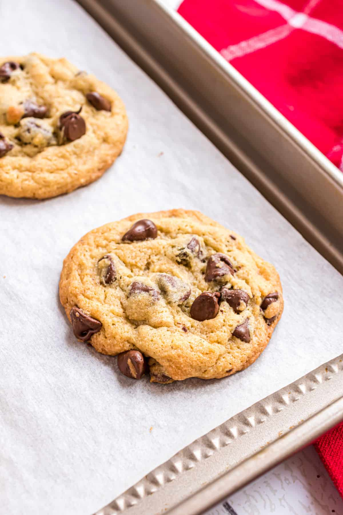 Chocolate chip pudding cookies on parchment paper lined cookie sheet.