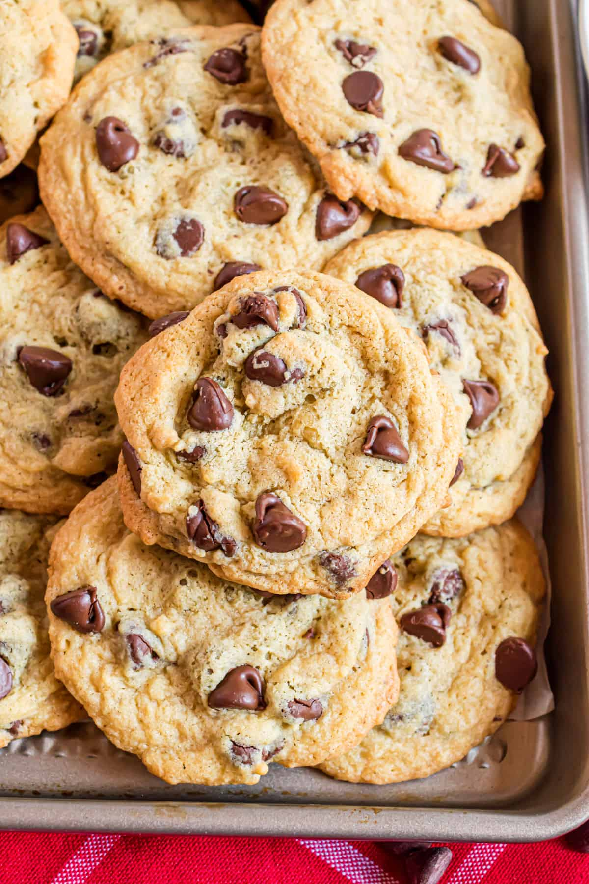 Baking sheet stacked with chocolate chip cookies.