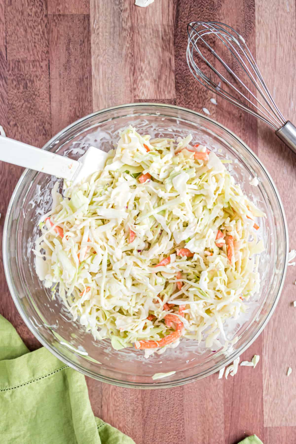 Creamy coleslaw in a clear glass bowl with white spatula.