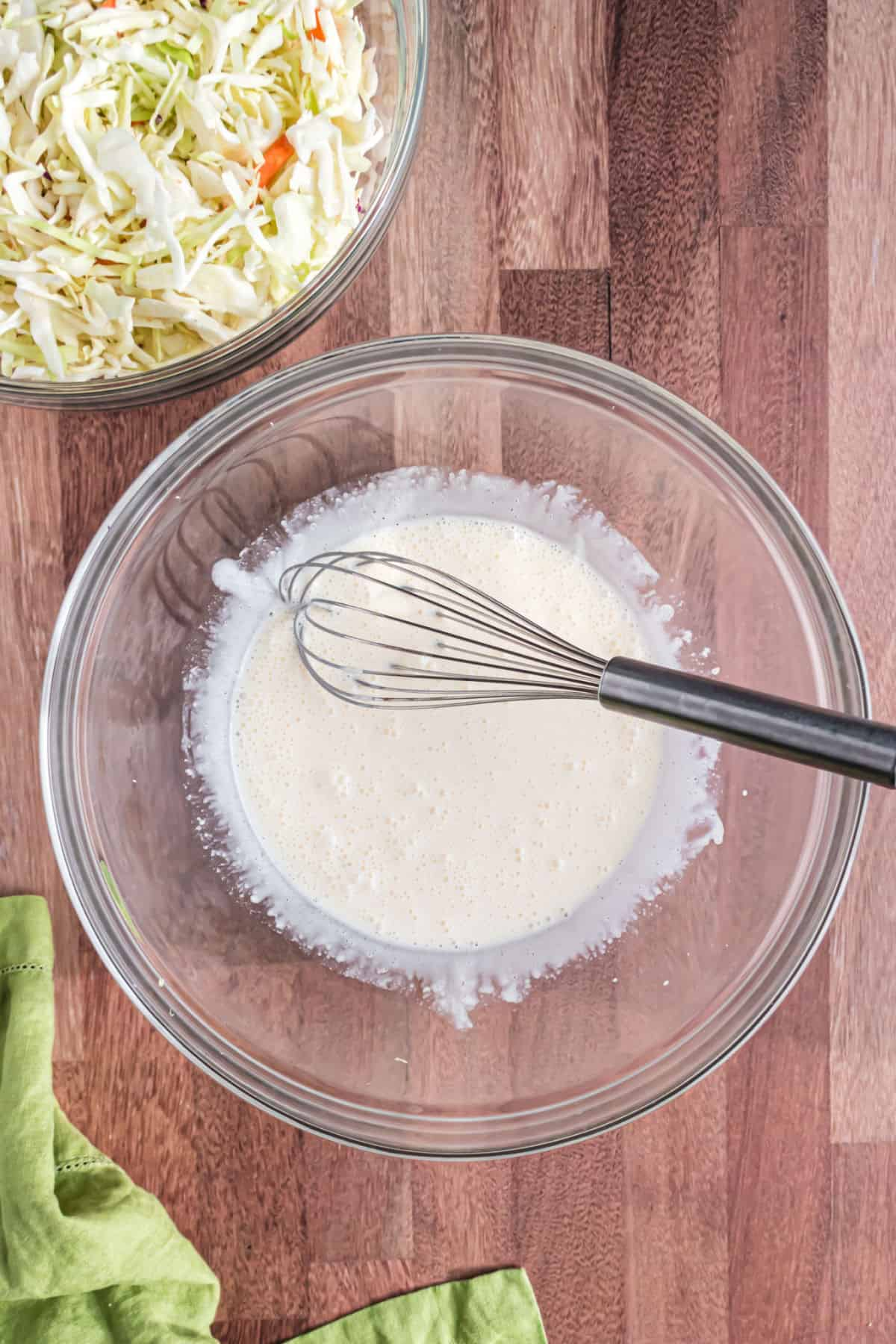 Dressing for coleslaw in a clear glass bowl with a whisk.