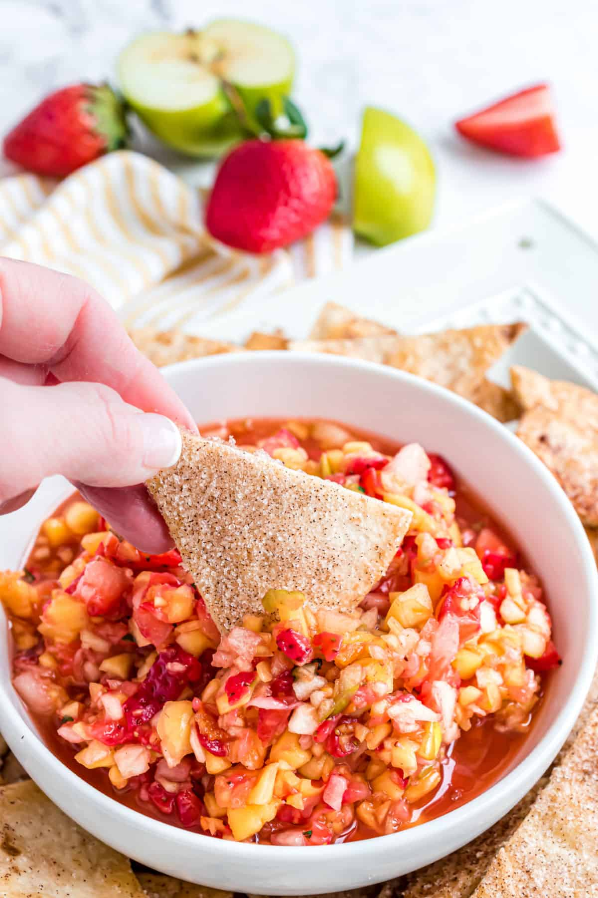 Fruit salsa in a white bowl with homemade cinnamon tortilla chips.
