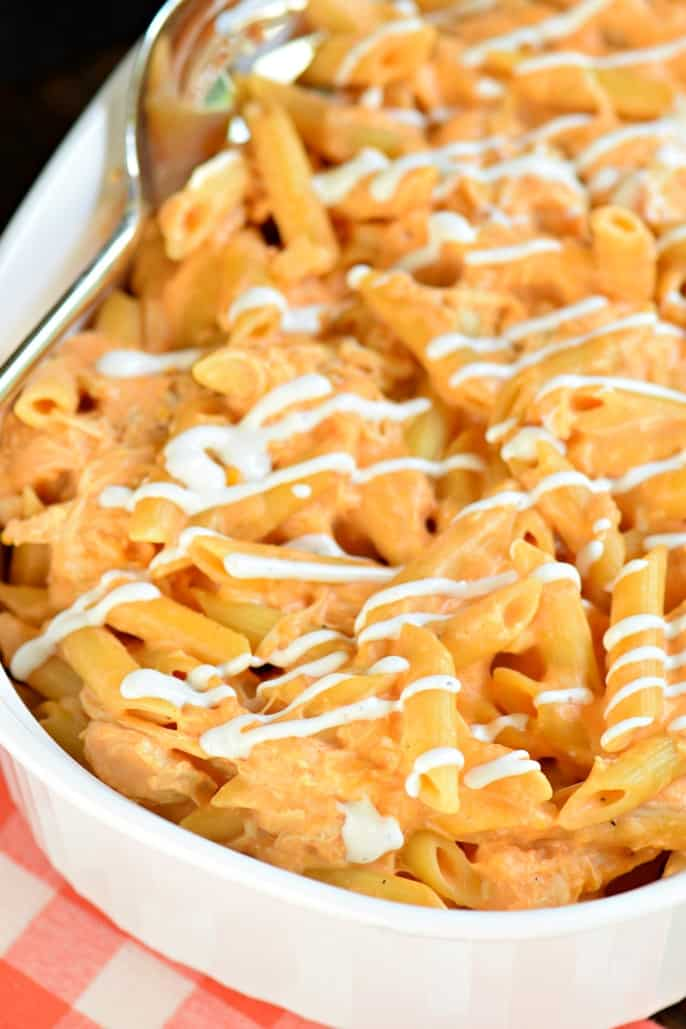 Buffalo chicken pasta in a white casserole dish topped with ranch dressing.