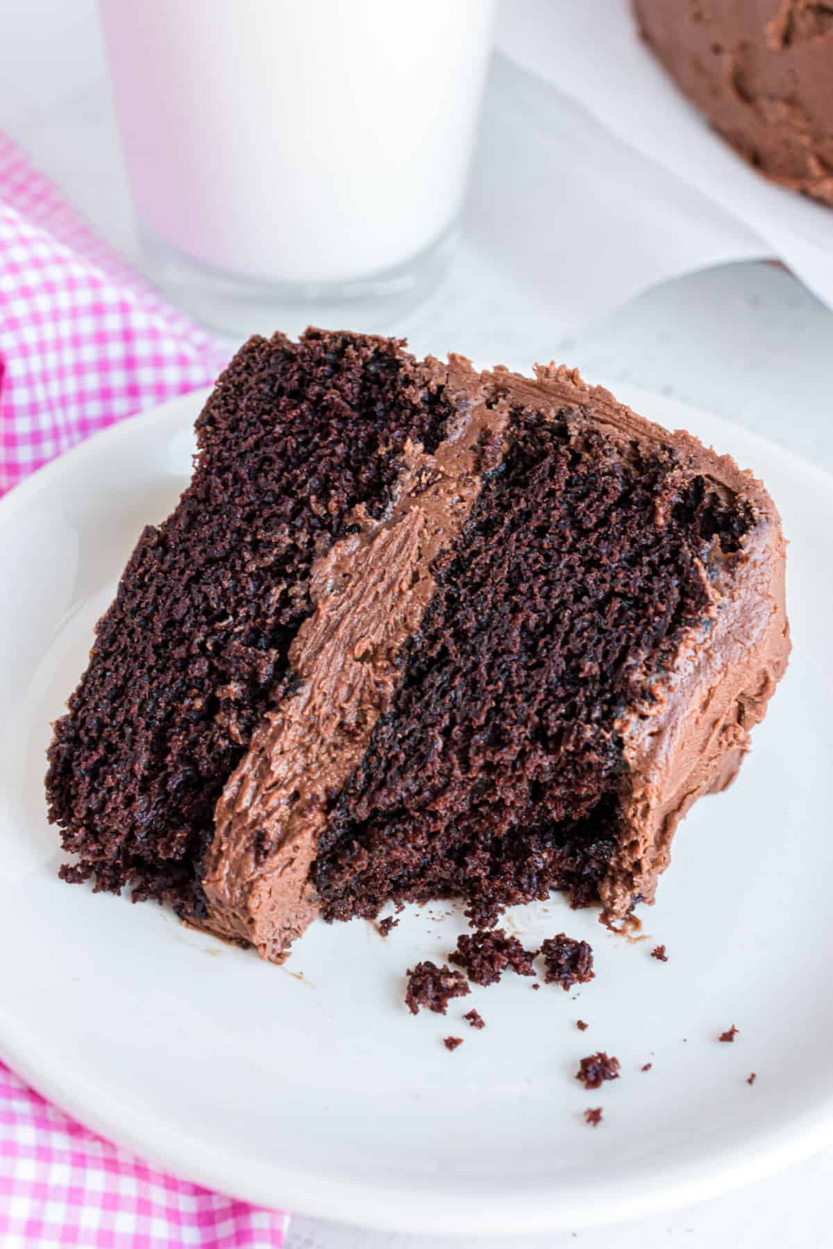 Slice of chocolate layer cake on a white plate with a bite removed and soft crumbs exposed.