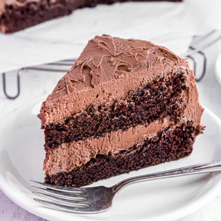 Double layer chocolate cake with chocolate frosting on a white plate.