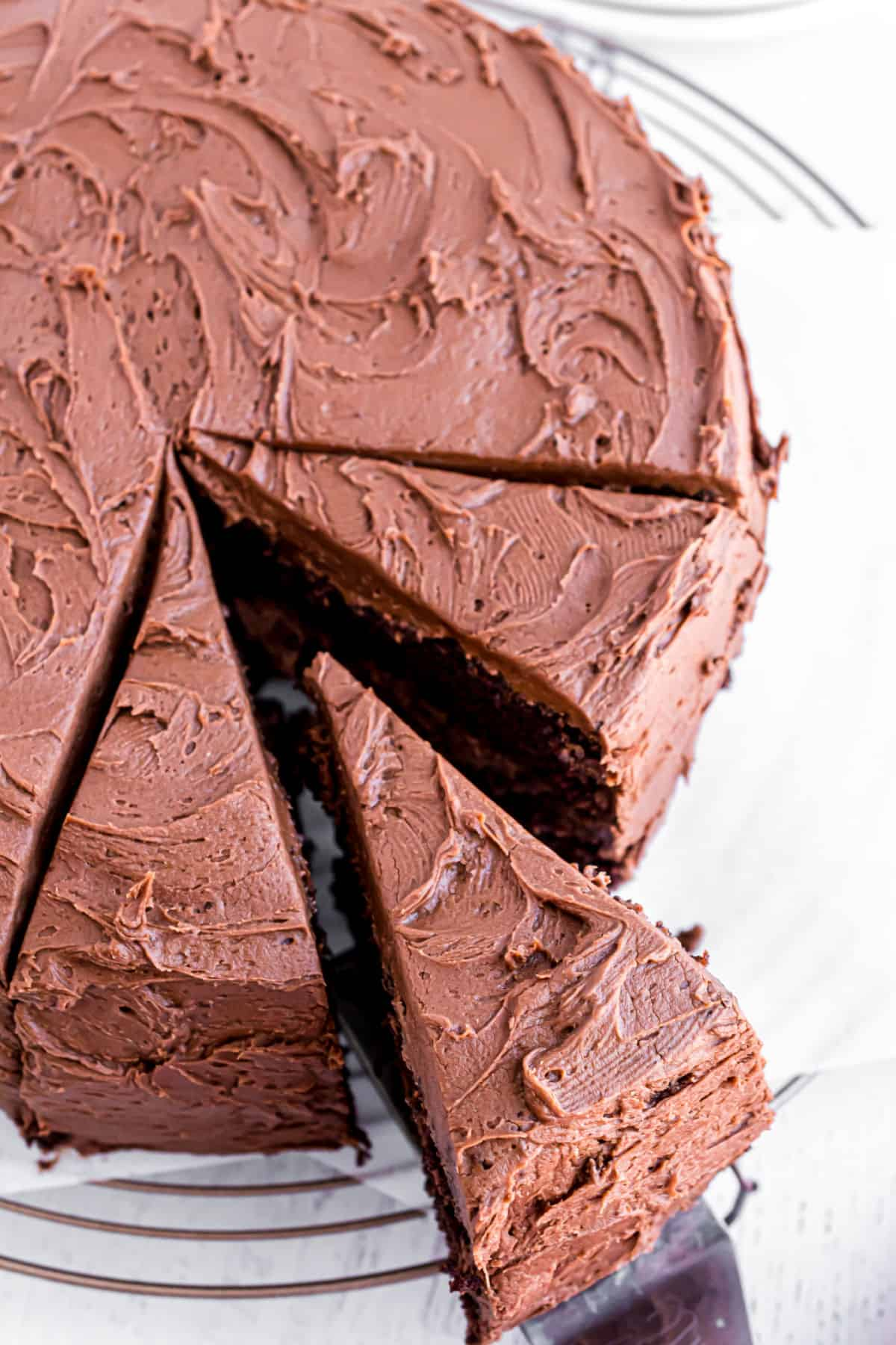 Whole chocolate layer cake with three slices cut and one being removed with a spatula.