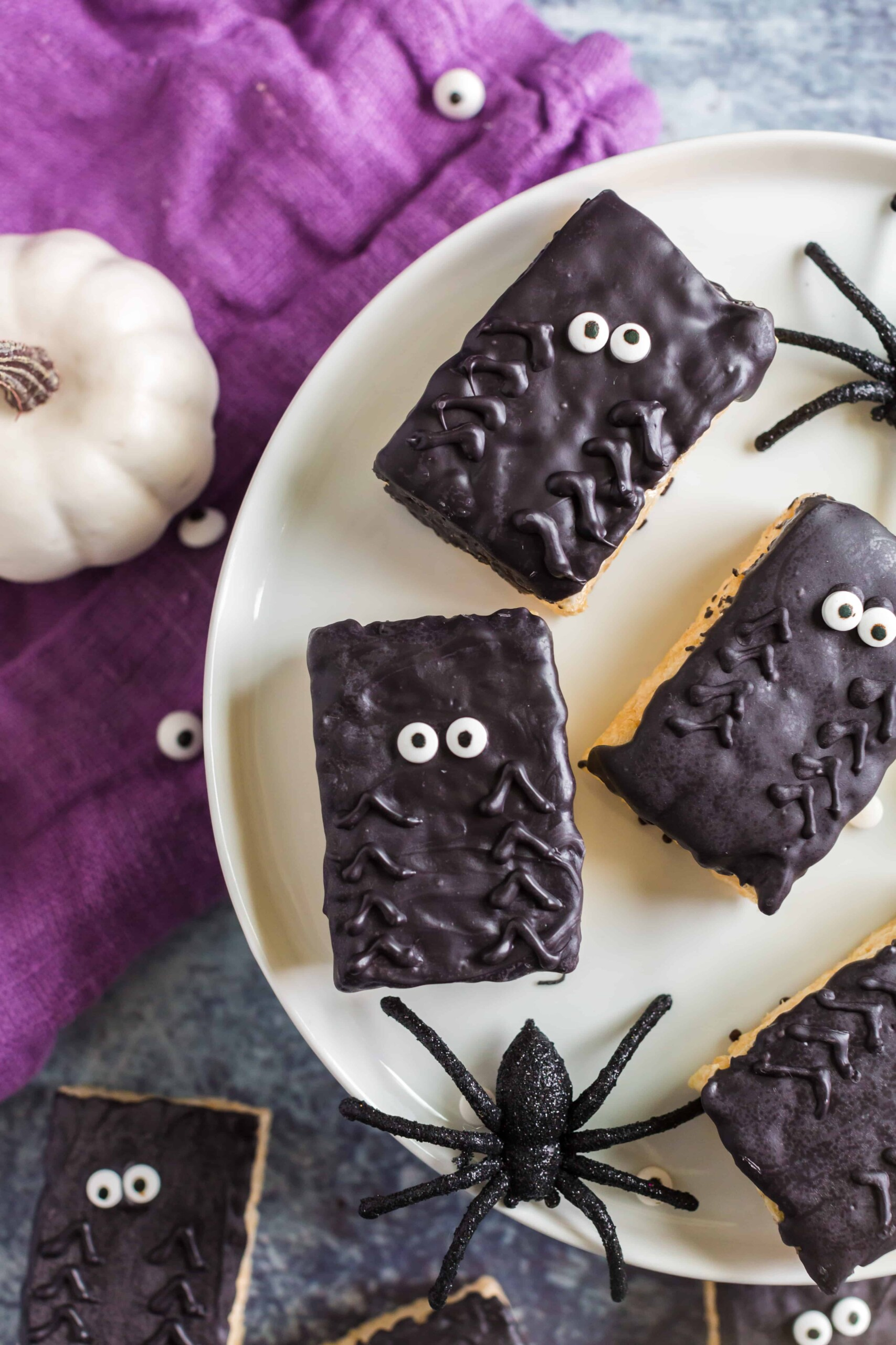 Plate with rice krispie treats decorated with chocolate and candy eyes to resemble spiders.