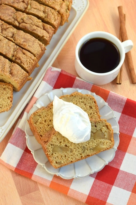 Two slices of apple bread with whipped cream and cup of black coffee.