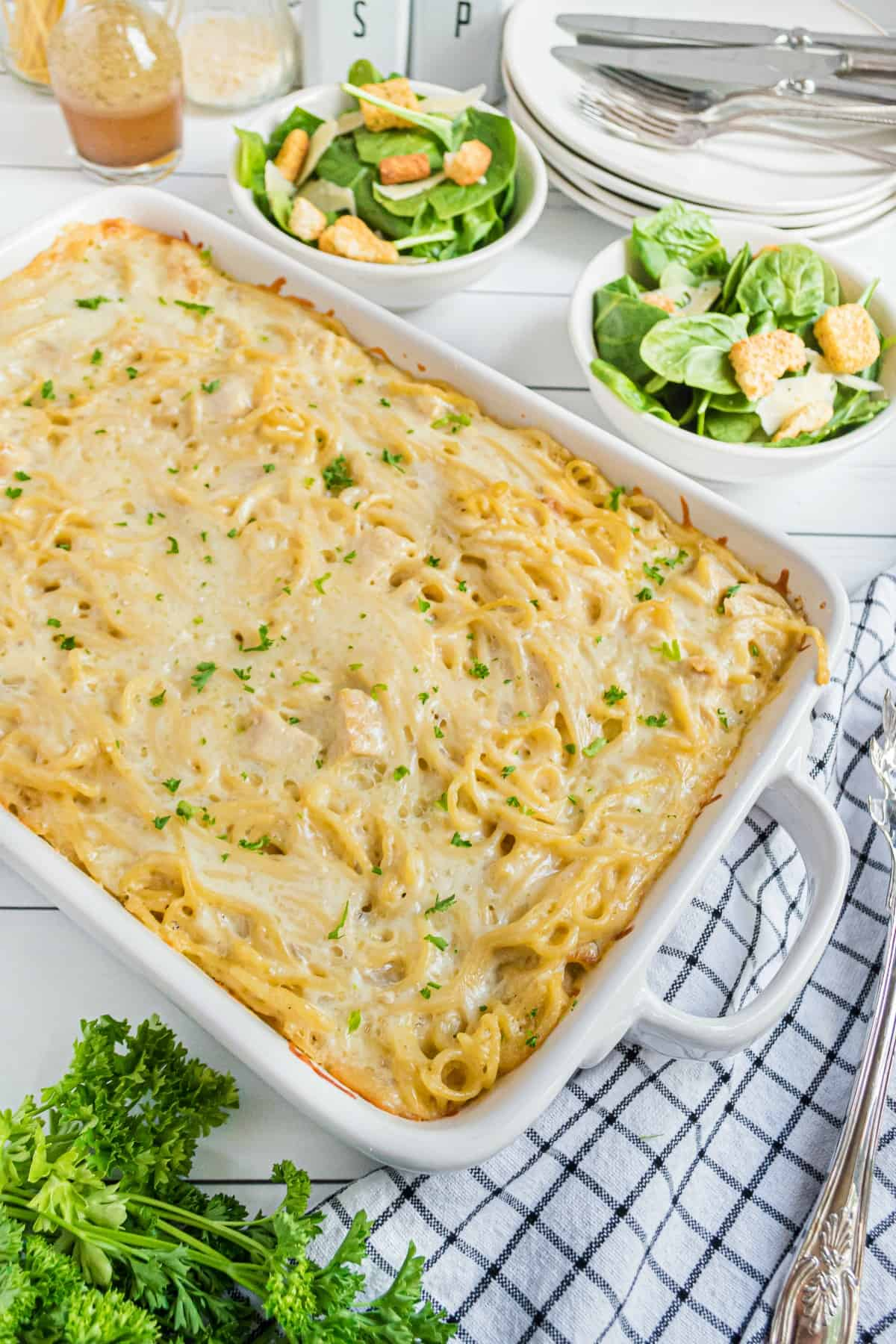 Chicken tetrazzini baked in a white 13x9 dish and served with a green side salad.