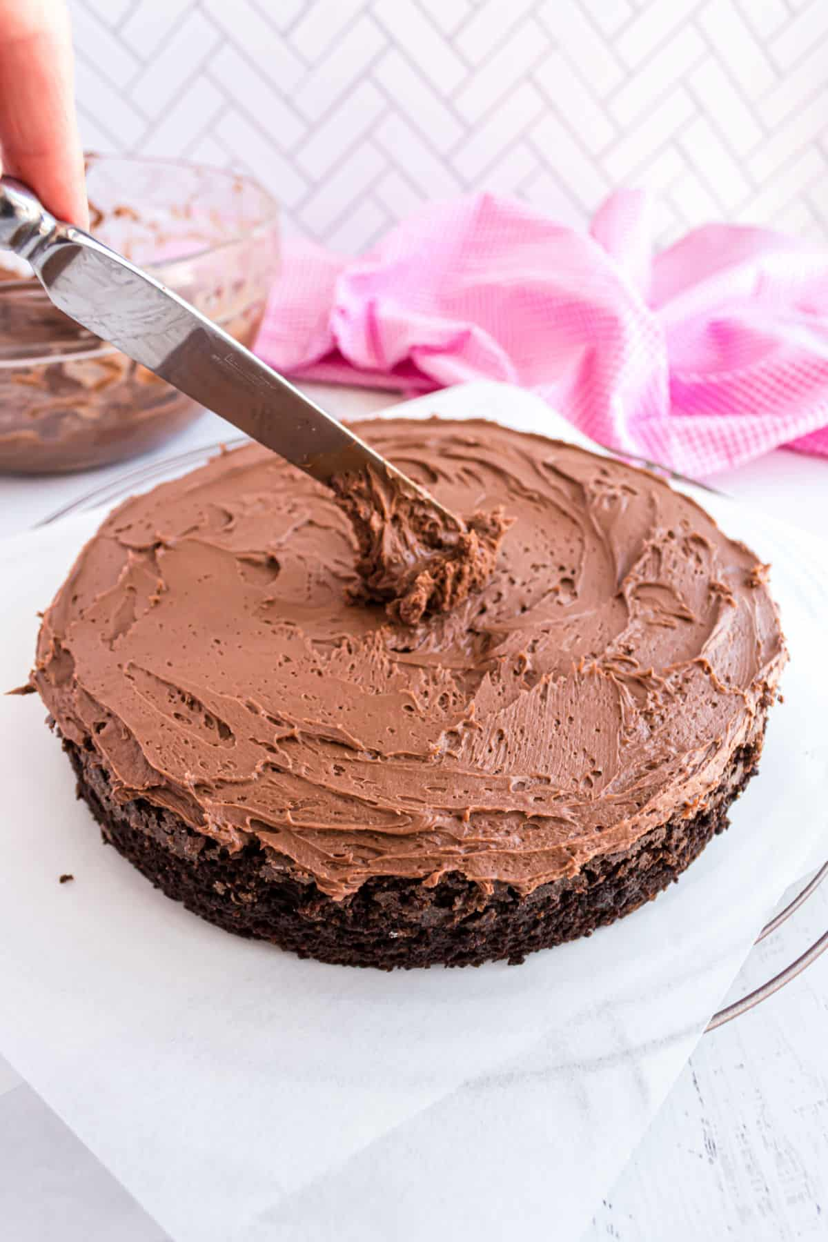 Chocolate frosting being added to a chocolate layer cake.